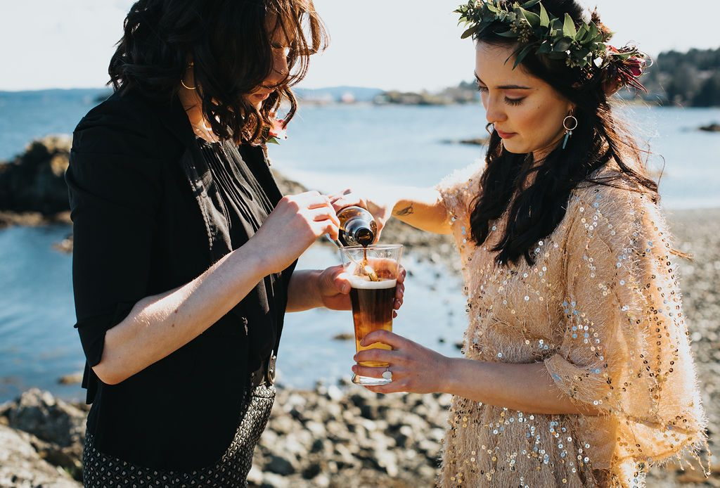 same sex couple pouring a black and tan in an elopement ceremony on the beach